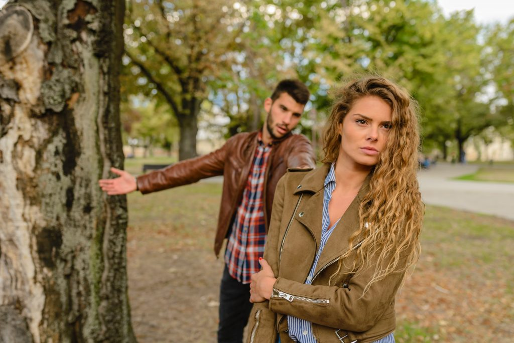 Bildquelle: pexels -- Im Vordergrund ist eine Frau mit bitterer Miene, der Mann hinter ihr - beide im Park. Deutlich erkennbar haben sie einen Streit.