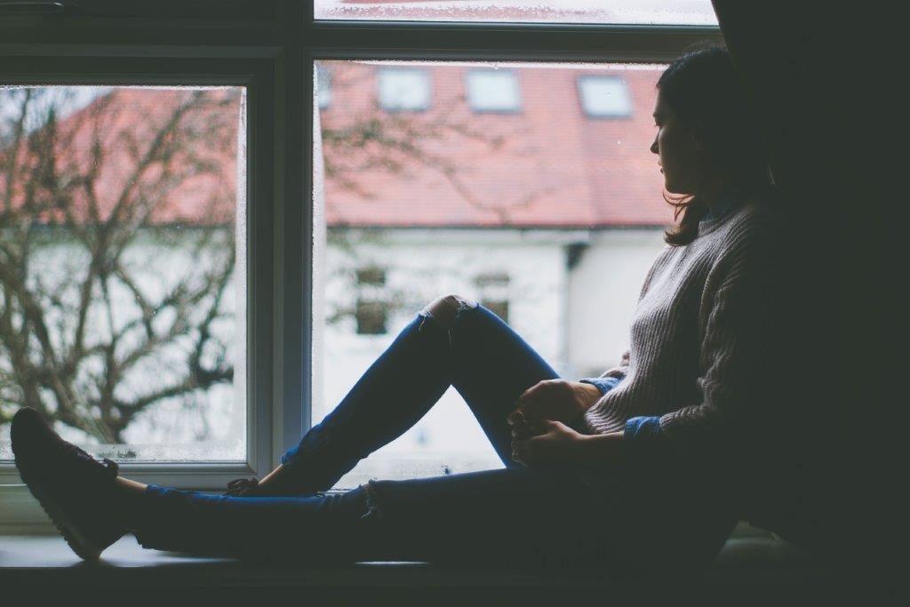 Herbst/Winter/trübe Jahreszeit: junge Frau sitzt auf einer Fensterbank und guckt nachdenklich hinaus © pixabay.com