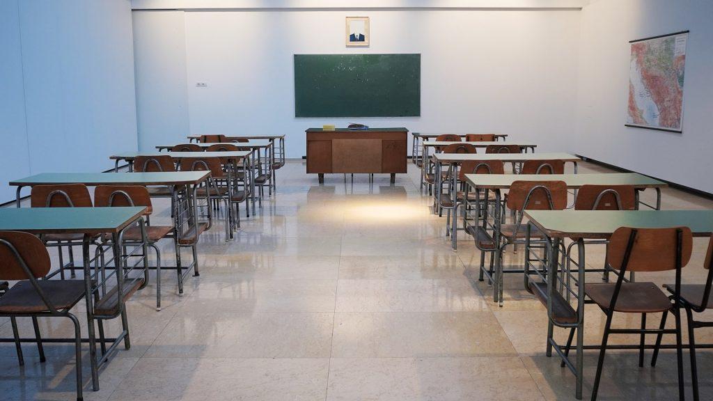 Leeres Klassenzimmer älteren Datums mit freiem Mittelgang, links und rechts je eine Reihe Schulbänke/Stühle und mittig am Kopfende des Raumes befinden sich Lehrertisch und grüne Tafel. Rechts an der Wand hängt eine Landkarte; Photo by Ivan Aleksic on Unsplash