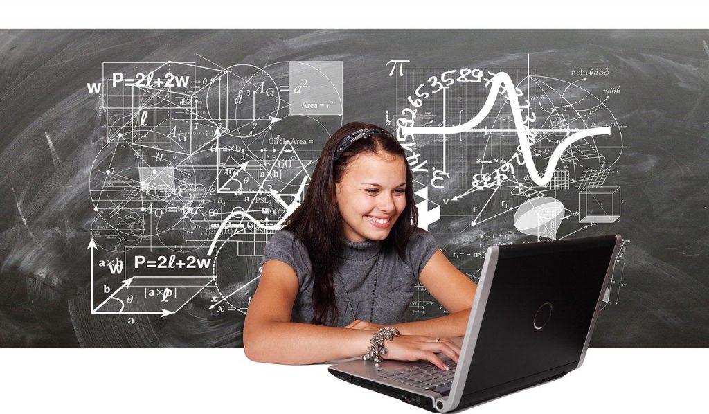 Lächelndes Mädchen sitzend vor einem Laptop - vor einer mit Formeln überfrachteten Tafel: Sinnbild für positives Lernen; Bild von Gerd Altmann auf Pixabay