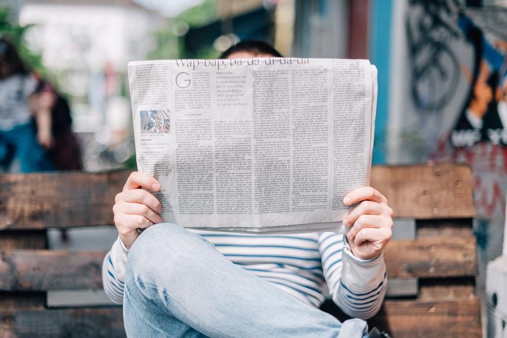 Man sitzt auf einer Bank und liest eine Zeitung. Photo by Roman Kraft @romankraft on Unsplash - https://unsplash.com/photos/_Zua2hyvTBk