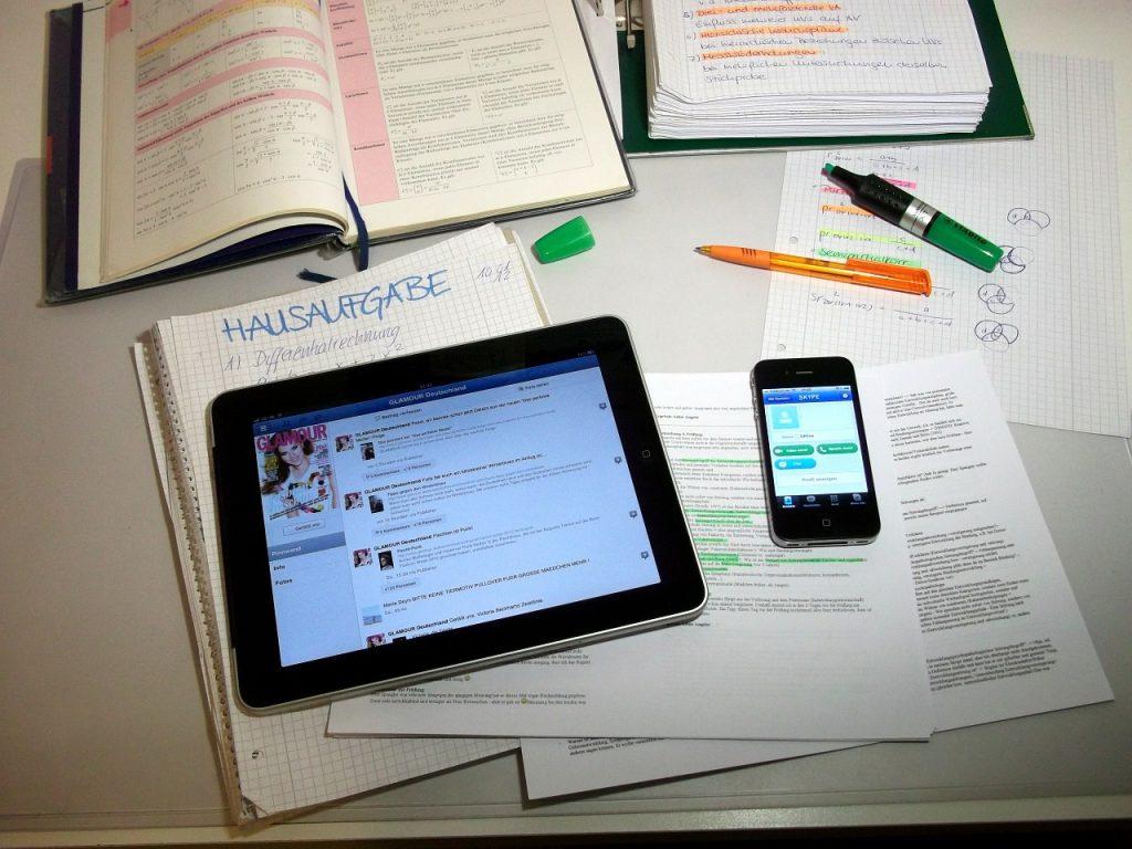 Auf einem Tisch befinden sich Schulbuch, Hefte, elektronisches Tablet und Smartphone zur Anfertigung von Hausaufgaben; Bild von Liane Kwoll auf Pixabay