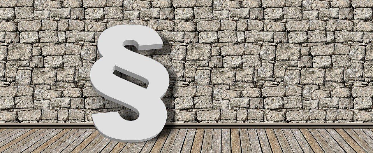 Symbol eines Paragrafen (weiß) vor einer grauen Steinmauer; Bild von Gerd Altmann auf Pixabay