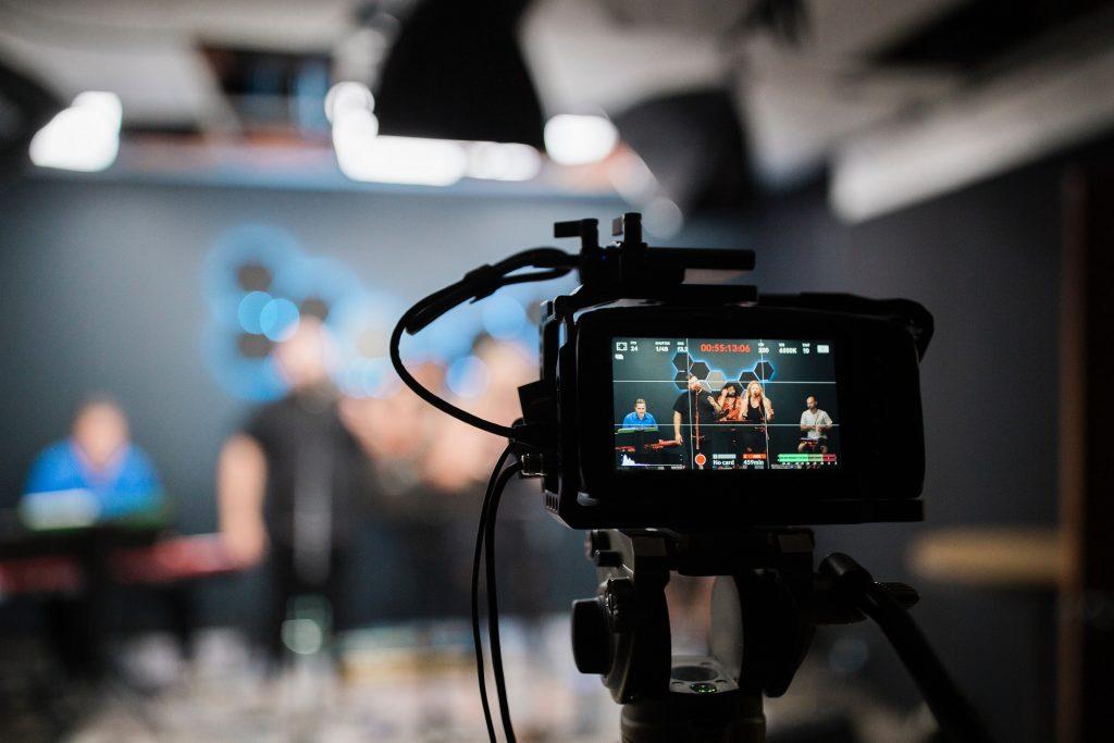 Kamera zeichnet eine Sendung auf, im Fokus des Bildes steht die Kamera, auf der man das Gefilmte sieht, Hintergrund ist verschwommen; Bild: unsplash.com @jesuslovesaustin