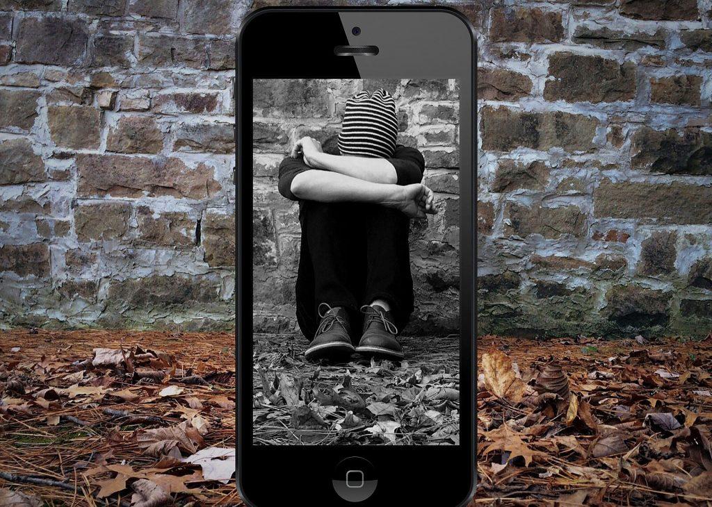 Trauriger Junge vor einer Steinwand – Kopf auf den angezogenen Knien gesenkt – gerahmt von einem Smartphone; Bild von un-perfekt auf Pixabay
