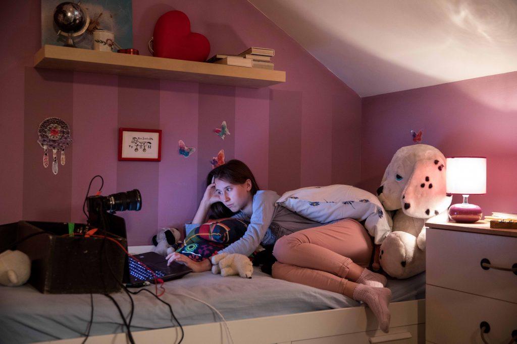 Rosa Kinderzimmer: Mädchen beim Chatten auf Bett liegend vor ihrem Laptop (+Kamera) | Darstellerin Sabina Dlouhá beim Chatten in GEFANGEN IM NETZ // © Hypermarket Film / Filmwelt Verleihagentur